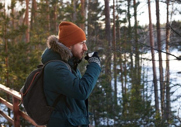Retrato de um homem barbudo bonito bebendo chá quente ao ar livre em viagem pela floresta a pé
