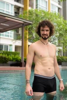 Retrato de um homem barbudo bonito com cabelo encaracolado sem camisa relaxando ao lado da piscina na cidade de bangkok, tailândia