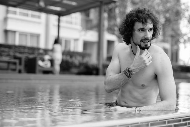 Retrato de um homem barbudo bonito com cabelo encaracolado sem camisa relaxando ao lado da piscina