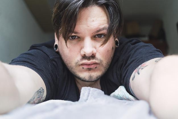 Retrato de um homem barbudo bonito com piercing e tatuagens