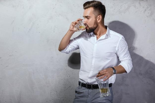 Retrato de um homem barbudo bonito com um copo de uísque