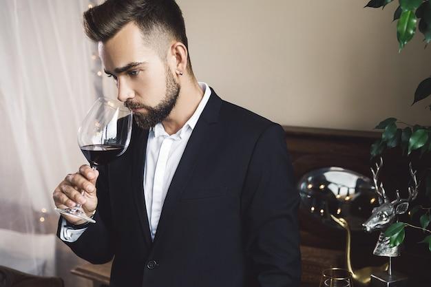 Retrato de um homem barbudo bonito com uma taça de vinho tinto