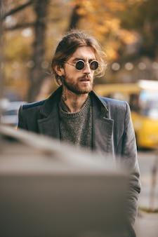 Retrato de um homem barbudo bonito em óculos de sol