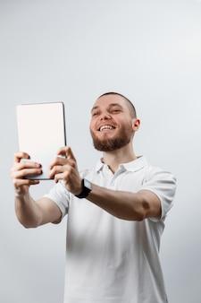 Retrato de um homem barbudo bonito em uma camiseta branca falando tablet chamando vídeo