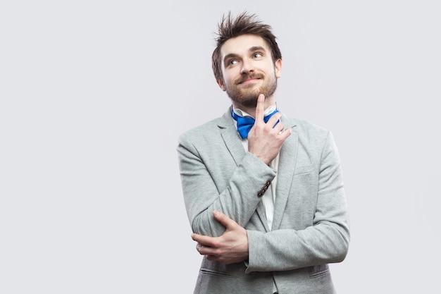 Retrato de um homem barbudo bonito feliz sonhador em casual terno cinza e gravata azul em pé e olhando para longe, sorrindo e sonhando. tiro de estúdio interno, isolado em fundo cinza claro.