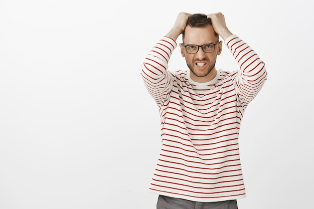 Retrato de um homem barbudo bonito irritado com raiva de óculos, tirando o cabelo da cabeça e fazendo uma careta de indignação, em pé sobre uma parede cinza em um pulôver listrado fofo, estressado