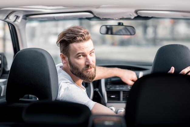 Retrato de um homem barbudo bonito olhando para trás, sentado no banco da frente do carro