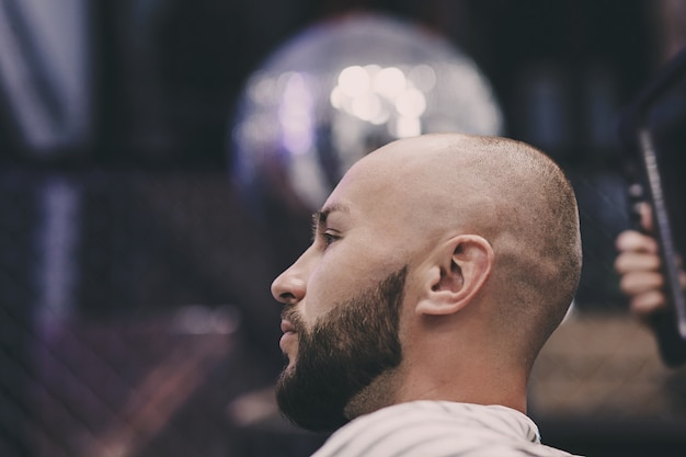 Retrato de um homem barbudo bonito sentado em uma cadeira em uma barbearia