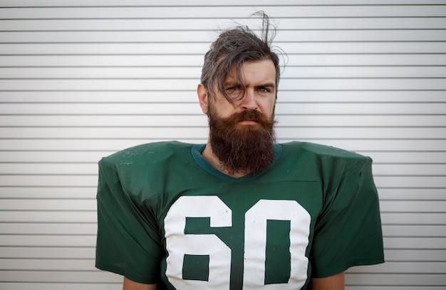 Retrato de um homem barbudo brutal com uniforme verde jogando futebol americano contra uma parede branca