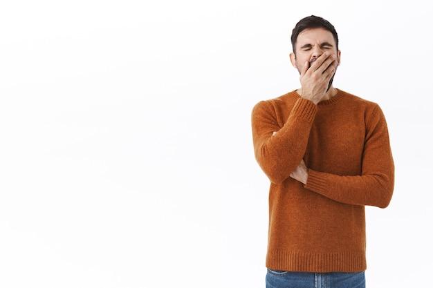 Retrato de um homem barbudo cansado se sentindo exausto depois de trabalhar tarde da noite, bocejando e cobrindo a boca com a palma da mão, entediado ou com sono, esperando a xícara de café da manhã no escritório, parede branca