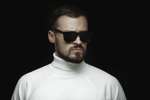 Retrato de um homem barbudo com um suéter branco e óculos escuros com uma aparência intensa em pé dentro de casa
