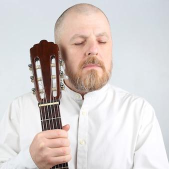 Retrato de um homem barbudo com um violão clássico na mão