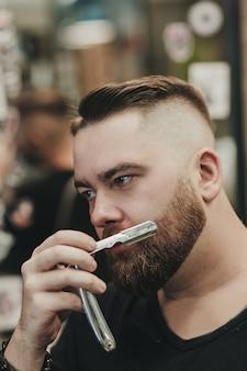 Retrato de um homem barbudo com uma navalha em uma barbearia