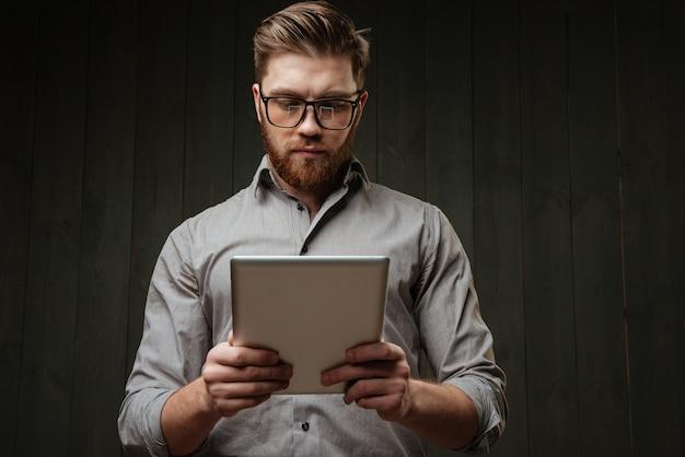 Retrato de um homem barbudo concentrado em óculos e camisa usando computador tablet isolado na superfície de madeira preta