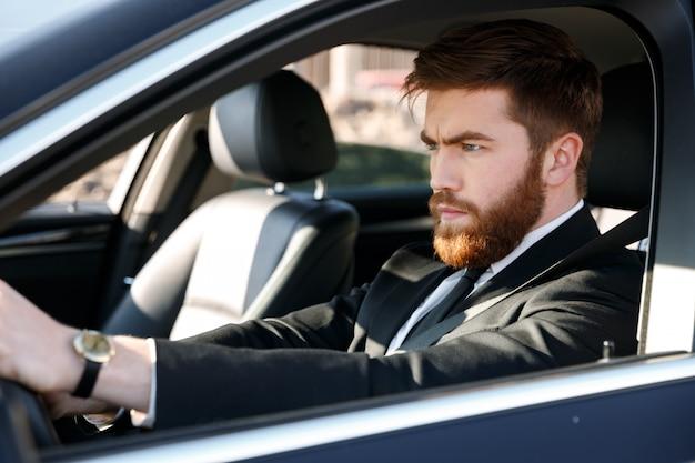 Retrato de um homem barbudo concentrado em terno dirigindo carro