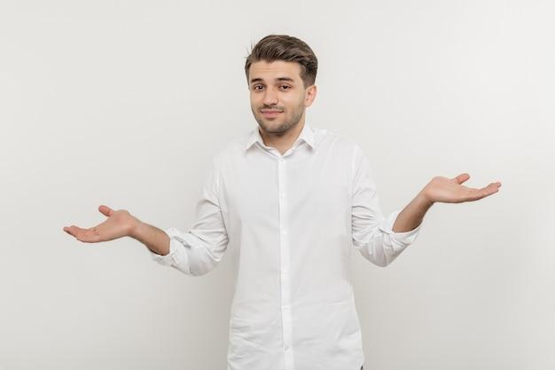 Retrato de um homem barbudo confuso, vestido de maneira casual, isolado sobre os ombros brancos, encolhendo os ombros