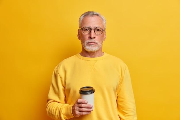 Retrato de um homem barbudo de cabelos grisalhos segurando uma xícara de café para viagem vestida com um macacão casual olhando diretamente para a frente, isolado sobre a parede amarela, satisfeito com o tempo livre