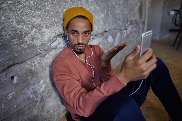 Retrato de um homem barbudo de olhos castanhos com pele escura olhando para a câmera com o rosto perplexo e levantando a palma da mão confusamente, posando sobre a parede de concreto em um suéter rosa, calças azuis, calças e boné mostarda