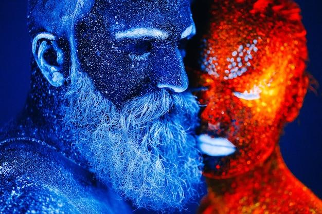 Retrato de um homem barbudo e uma mulher pintados em pó ultravioleta.