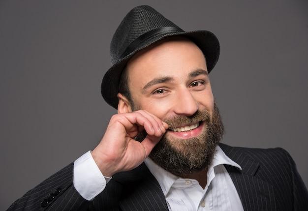 Retrato de um homem barbudo em um terno e um chapéu.