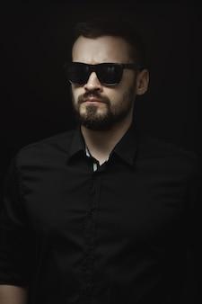 Retrato de um homem barbudo em uma camisa preta e óculos escuros com um olhar intenso dentro de casa