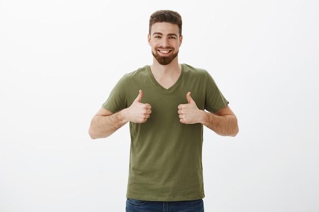 Retrato de um homem barbudo encantador, alegre e solidário com uma camiseta mostrando os polegares para cima e sorrindo