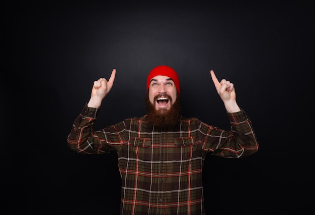 Retrato de um homem barbudo feliz apontando os dedos para cima em copyspace isolado sobre a parede escura