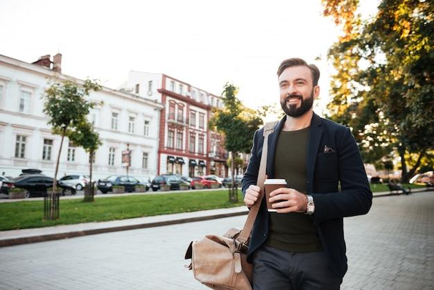 Retrato de um homem barbudo feliz bebendo café