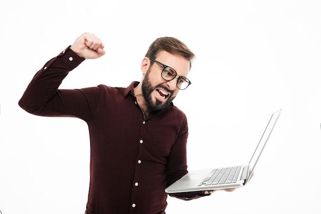 Retrato de um homem barbudo feliz segurando o computador portátil