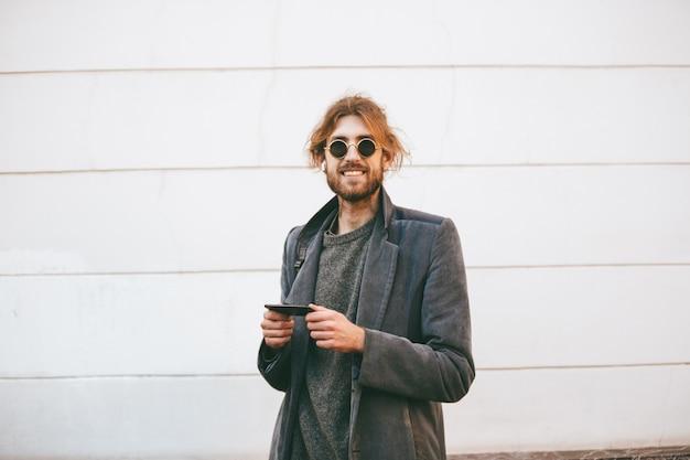 Retrato de um homem barbudo feliz usando óculos escuros