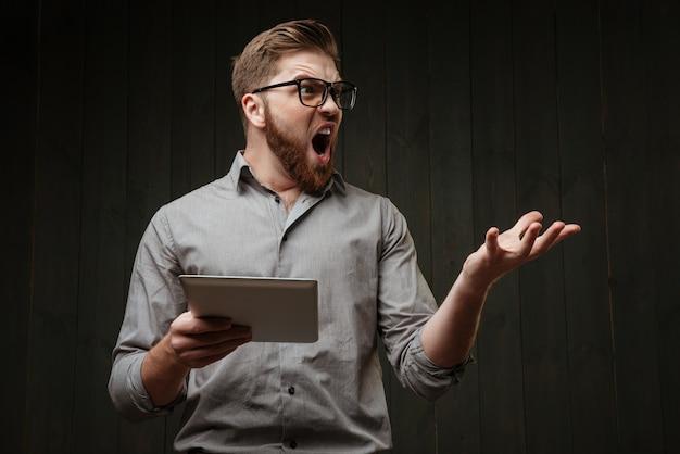 Retrato de um homem barbudo gritando em óculos, segurando um computador tablet e olhando para longe, isolado em uma superfície de madeira preta