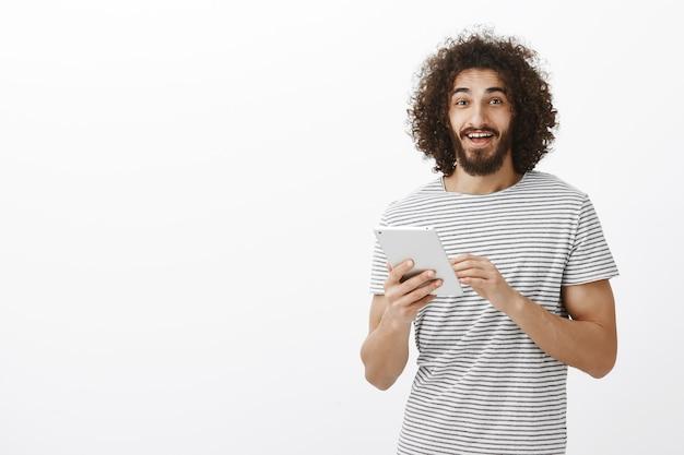 Retrato de um homem barbudo hispânico amigável e feliz com penteado afro, segurando o tablet digital branco e sorrindo para a tela, compartilhando notícias positivas com os amigos