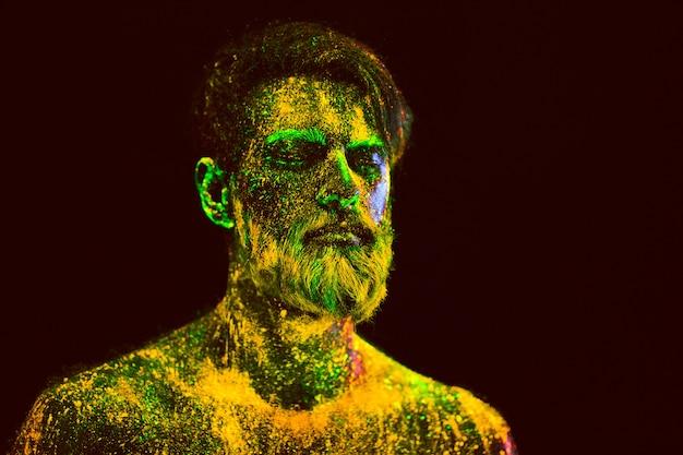 Retrato de um homem barbudo. homem é pintado em pó ultravioleta.