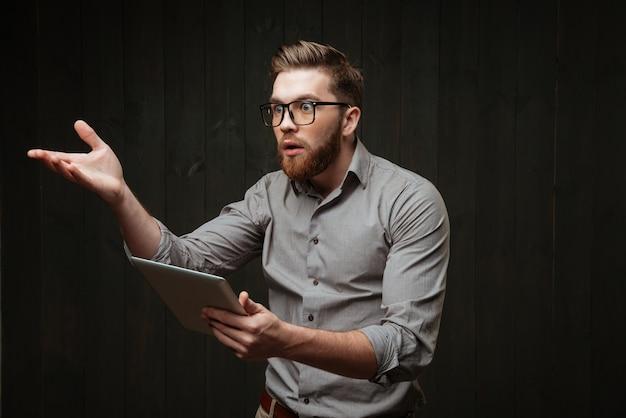 Retrato de um homem barbudo insatisfeito com óculos, segurando um computador tablet e gesticulando, isolado em uma superfície de madeira preta