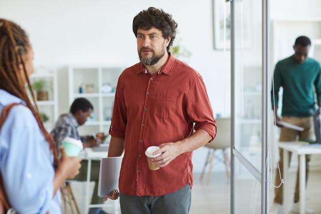 Retrato de um homem barbudo maduro vestido com roupa casual conversando com uma colega durante a pausa para o café no escritório