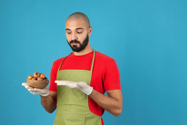 Retrato de um homem barbudo no avental segurando uma tigela de madeira com frutas secas.