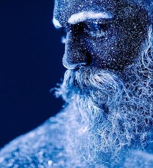 Retrato de um homem barbudo, o homem é pintado em pó ultravioleta.