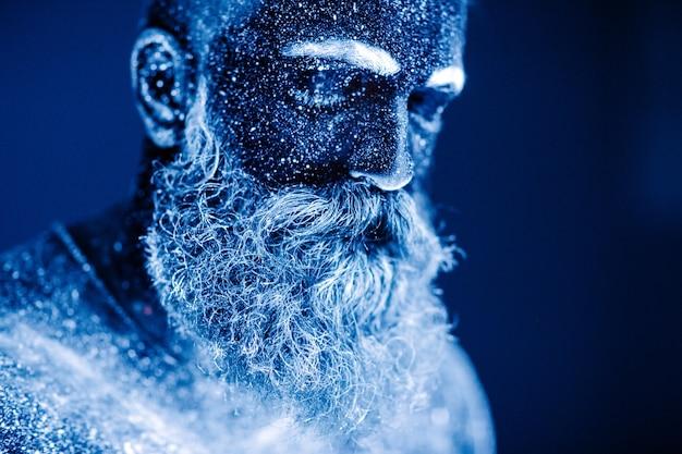 Retrato de um homem barbudo. o homem é pintado em pó ultravioleta.