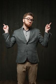 Retrato de um homem barbudo perplexo em óculos e terno apontando os dedos isolados no fundo preto de madeira