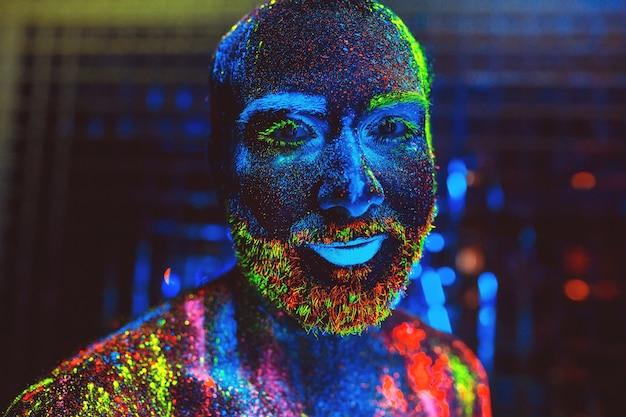 Retrato de um homem barbudo pintado em pó fluorescente.