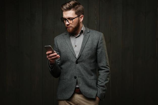 Retrato de um homem barbudo sério em um terno casual em pé com o celular isolado no fundo preto de madeira