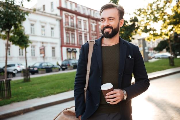 Retrato de um homem barbudo sorridente bebendo café
