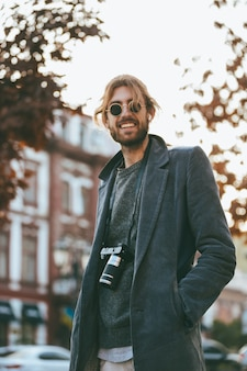 Retrato de um homem barbudo sorridente com câmera