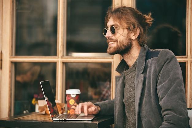 Retrato de um homem barbudo sorridente em fones de ouvido sentado ao ar livre