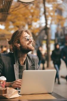 Retrato de um homem barbudo sorridente em fones de ouvido