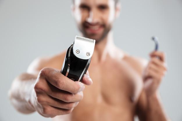 Retrato de um homem barbudo sorridente feliz mostrando barbeador elétrico