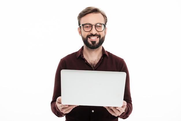 Retrato de um homem barbudo sorridente segurando o computador portátil