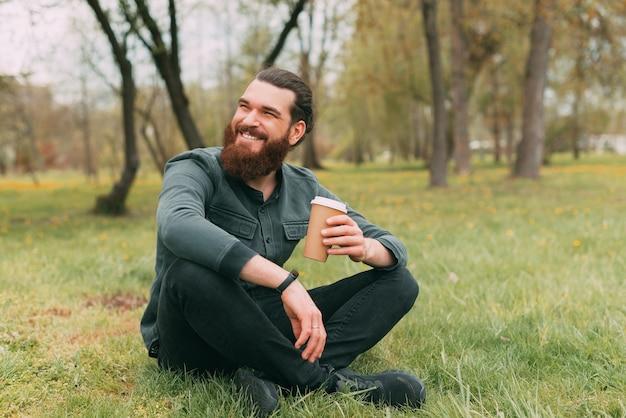 Retrato de um homem barbudo sorridente, sentado no parque na grama e bebendo uma xícara de café