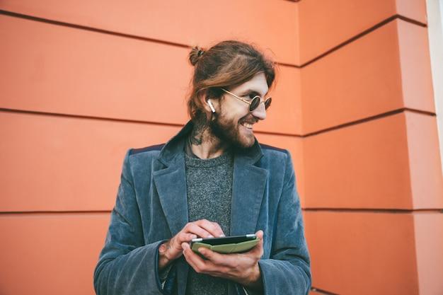 Retrato de um homem barbudo sorridente, vestido com casaco