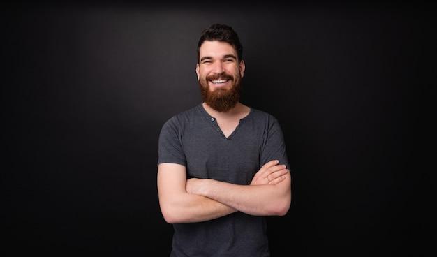Retrato de um homem barbudo sorrindo com as mãos cruzadas em pé sobre um fundo escuro
